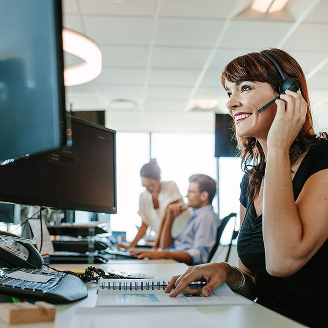 Businesswoman talking on her headset at her desk