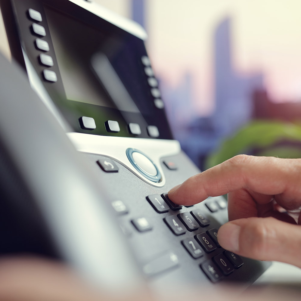 closeup of someone dialling on a desktop phone