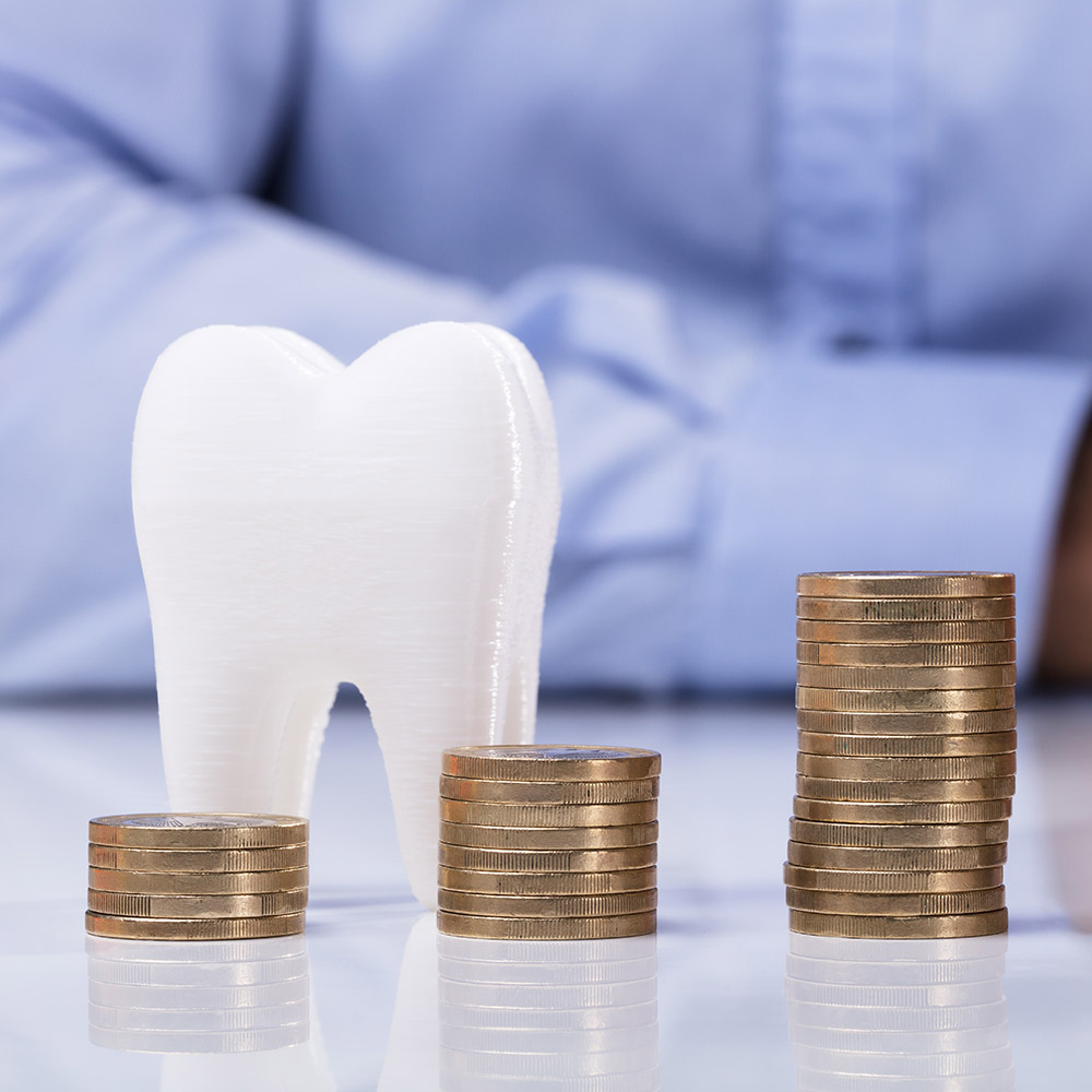 close up of a large plastic tooth and coins stacked on top of each other